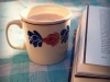 Cup of coffee next to a book