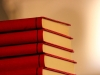 A stack of five red books with a warm glow around it
