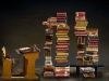 A photo of an antique student desk facing several stylishly designed stacks of books