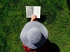 Person wearing a hat and laying in green grass reading a book.