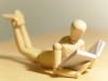 A close-up photograph of a small, wooden figure reading a tiny book.