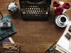 A top down shot of a writing desk with a manual typewriter, some plants, a cup of coffee, and implements associated with printmaking.