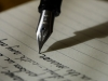 An old-style fountain pen writes on lined paper.