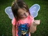 A photograph of a young girl with wet hair in a pink t-shirt watching a bug crawl on her closed hand. She is wearing a pair of translucent wings.