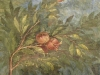 A painting of a pomegranate still on the branch done al fresco on an ancient and cracking wall