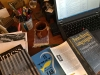 A top down photograph of a desk cluttered with books and a computer monitor nearby