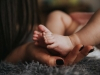 A close up photograph of a mother holding her baby's feet