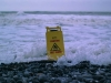 """A """"Caution: Wet Floor"""" sits on a beach and is enveloped by the tide"""
