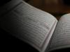 An open book written in Arabic, mostly shrouded in shadow