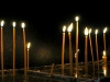 Thin, tapered, and lit candles arising from water