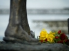 A close-up of a human foot in statue form with flowers laid before it