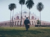 A man in the foreground walks toward Humayun's Tomb, partially shrouded in fog, in New Delhi