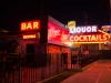 A desultory looking bar, decked with neon signs, presumably in Las Vegas