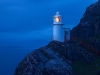 A photograph of a lighthouse perched on the face of a cliff, shrouded in blue dusk