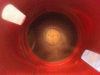 Coffee dregs sitting at the bottom of a red cup, as shot from above