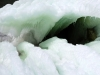 Thick sheets of ice warp to reveal a dark hole within