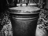 A black and white photograph of a black metal pail