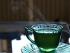 A photograph of a cup of tea. The cup is clear and the tea is green
