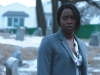 A woman in a blue suit looks just off-panel with a snowy suburban scene behind her