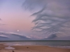 A beach dissolves into a shallow sea, beneath a purpled sky laced with wispy clouds