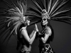 Two indigenous people, dressed in ceremonial makeup and dress, stand facing one another, palms touching
