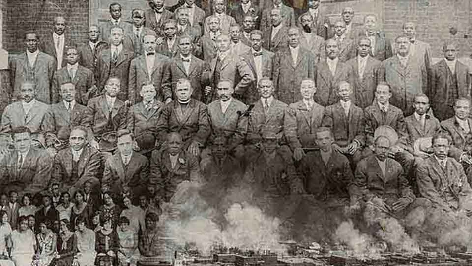 A collage composed of three photos. A black and white photograph of a group of black men dressed in suits. A photo of women similarly posed is overlain in the lower left hand corner and a photo of Tulsa burning overlain in the bottom right hand corner.
