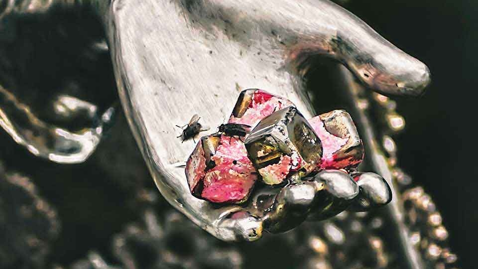 A photograph of a cluster of metal nuts, covered in some kind of red substance, inside of the hand of a metal statuary. A few flies linger in the palm.