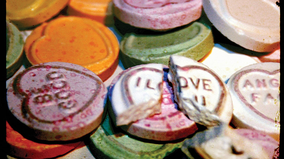 """A pile of conversation hearts with one that reads """"I Love You"""" broken at the top of the pile"""