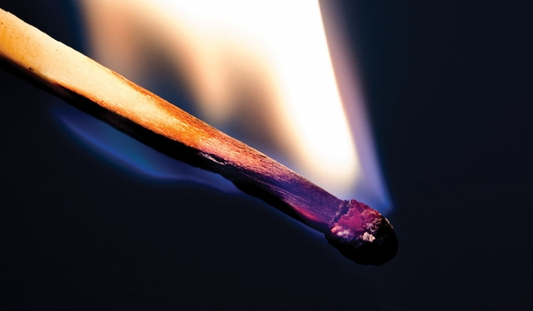 A close-up photograph of a wood match burning