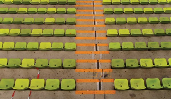 The empty seats of a soccer stadium as soon while looking down toward the field (which is not in the panel)