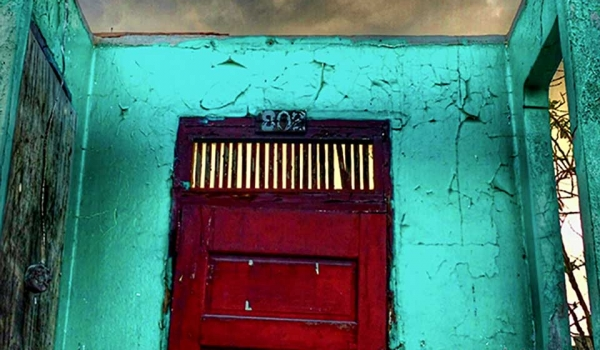 A photograph of a red door inset into a wall that has no roof, with the sky glowering in green-orange above