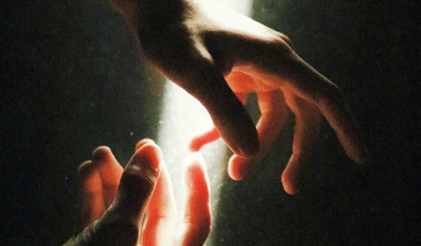 A pair of hands in a dark space illuminated by light from above