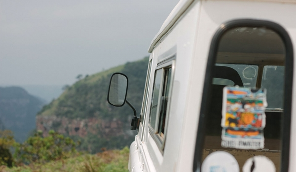 A photograph taken from directly behind a white vehicle as it travels on a wilderness landscape