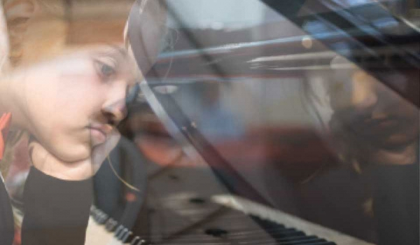 A photograph of a young woman looking glumly at a piano keyboard. The viewer is looking at her through a pane of glass