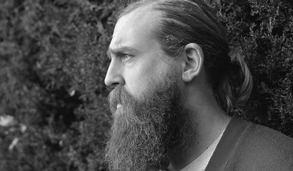 A black and white photograph of a bearded man standing in front of a tall hedge