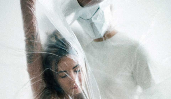 A photograph of a woman with her eyes closed, under a sheet of plastic. A figure dressed like a doctor stands above her on the other side of the plastic