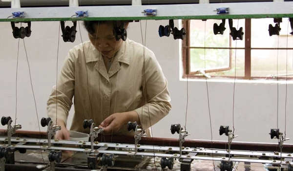 A woman stands on the production line of an industrial garment factory