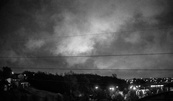 A black and white photograph of a hill, silhouetted against the growing dusk