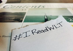 The hashtag #IReadWLT written on a sheet of paper with the magazine in the background