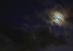 Crescent moon behind clouds. Photo by Adam Evans/Flickr