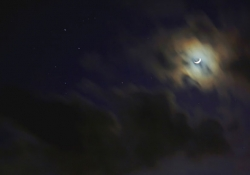 Crescent moon behind clouds. Photo by Adam Evans/Flickr