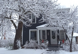 A blue house with snow on the roof and trees.