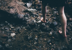 A woman walking over rocks with bare feet.