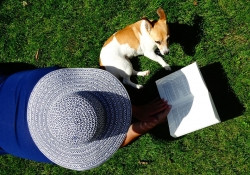 Woman reading book outside in green grass with a terrier.