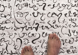 A pair of bared feet rest on a cloth covered in a non-English script.