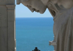 A statuary in the extreme foreground with the sea in the deep background.
