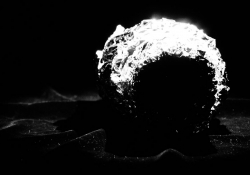 A black and white photo of a ball of aluminum foil, shrouded in darkness, except for a strip of focused light on its right side.