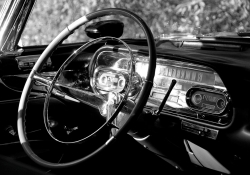 A black and white photograph of the interior of a vintage Cadillac with the focus on the steering column and gauges