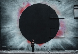 A photograph of a woman standing in front of the wall of an industrial looking building with a spray-painting of a black hole on the side of it