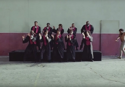 """A still image from the video to Childish Gambino's """"This is America,"""" featuring a choir of African-Americans singing on riser as Gambino emerges into the frame from the right"""